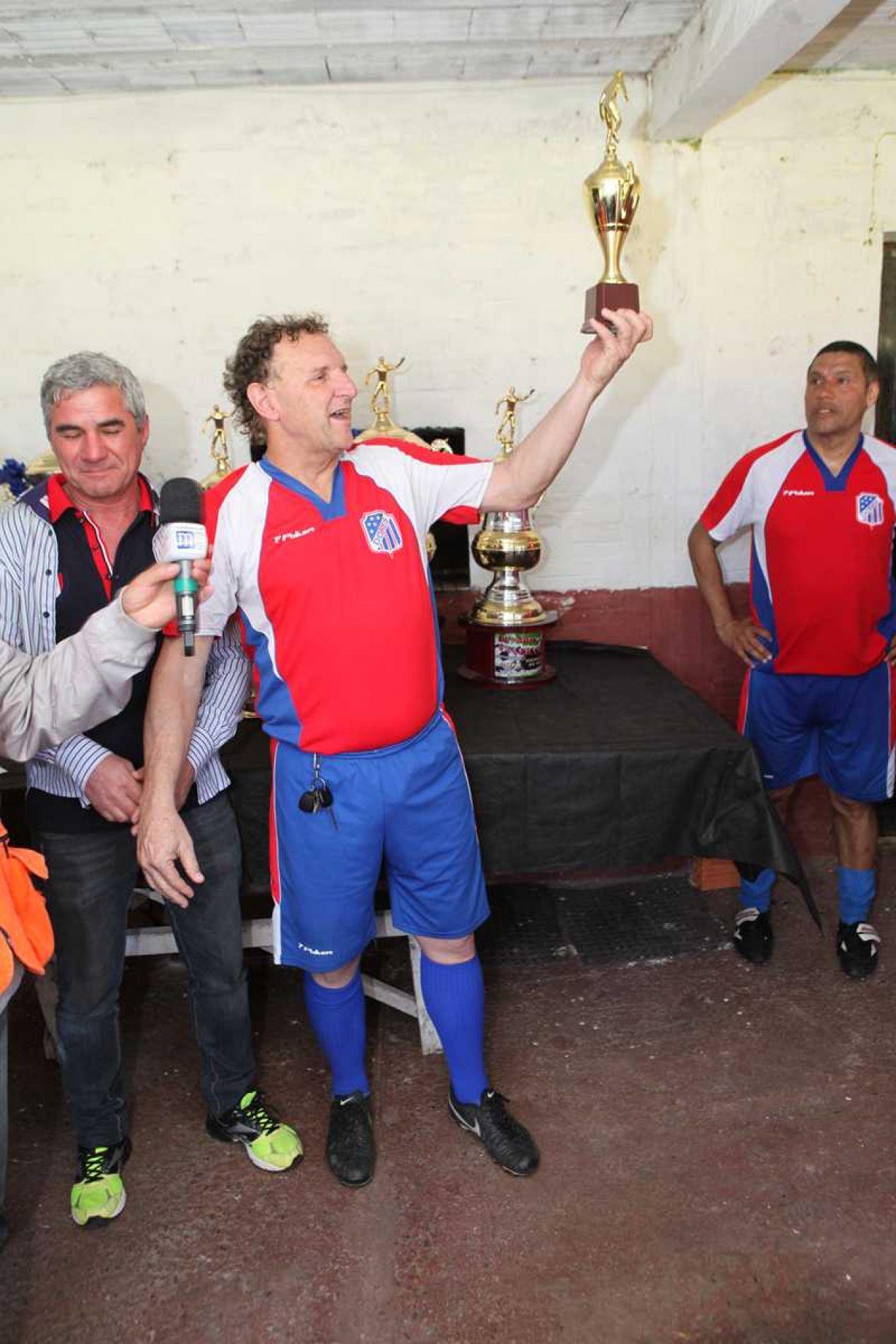Pelego, goleador da competição, exibe o troféu de campeão.