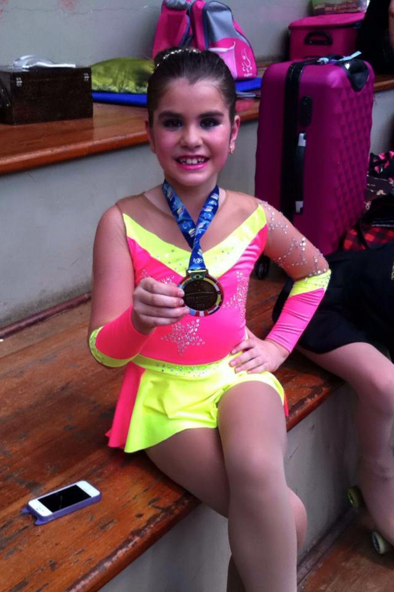 Mariana exibe uma medalha conquistada na patinação.