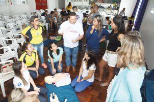 Giovane, ao centro, explica as especificidades dos protocolos de emergência para cada faixa etária às mães e professoras.